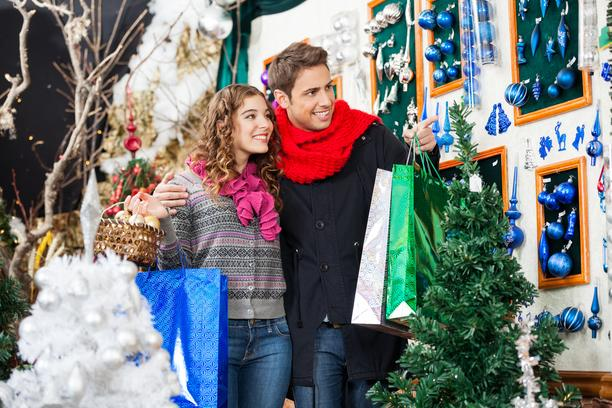 Happy young couple with bags shopping at Christmas store