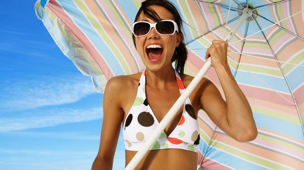 Young woman holding beach umbrella, smiling, portrait, close-up